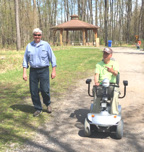 person on scooter and person walking together on a trail