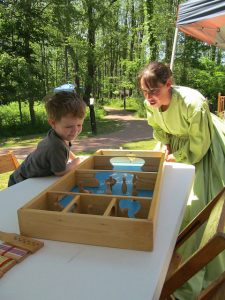 Woman helps child with old-fashioned table game